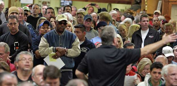 An auction ring man center, takes in bids during the auction of the late Dr. Michael Brown's estate at Webster's Auction Palace Sunday, Jan. 5, 2014, in Houston.  The sale of his items are part of a bankruptcy case still in progress in U.S. District Court. Photo: James Nielsen, Houston Chronicle / © 2013  Houston Chronicle