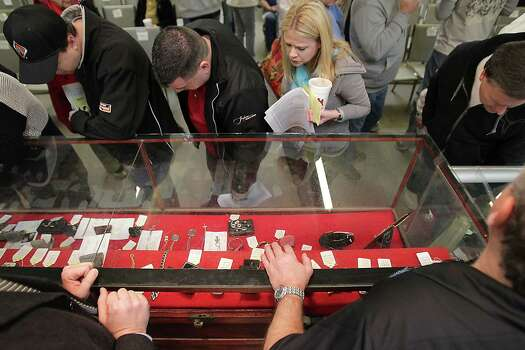 People look over jewelry items prior to the auction of the late Dr. Michael Brown's estate at Webster's Auction Palace Sunday, Jan. 5, 2014, in Houston.  The sale of his items are part of a bankruptcy case still in progress in U.S. District Court. Photo: James Nielsen, Houston Chronicle / © 2013  Houston Chronicle