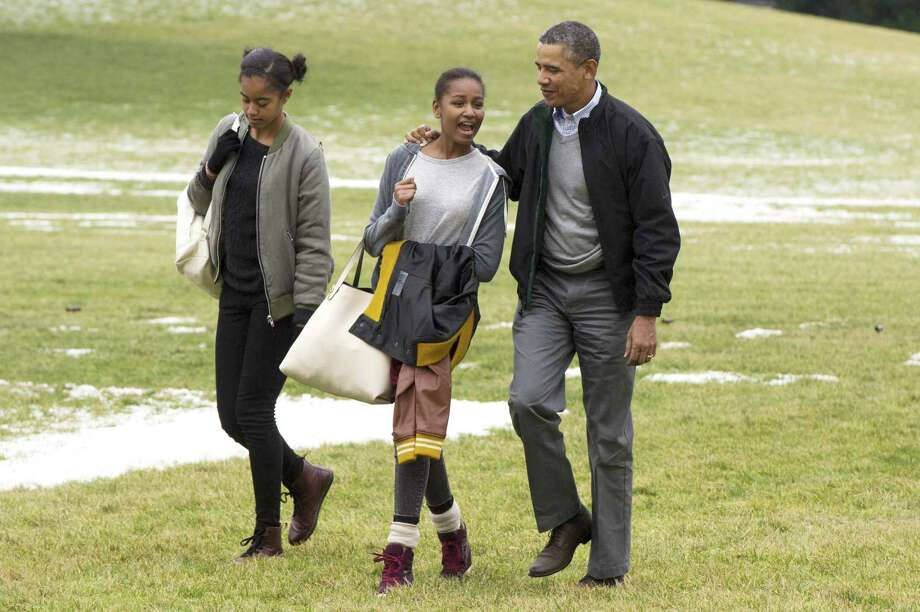 President Barack Obama and his daughters, Malia and Sasha, walk across the South Lawn of the White House after arriving Sunday by Marine One. They were returning from a two-week holiday in Hawaii. Photo: Pool / 2014 Getty Images