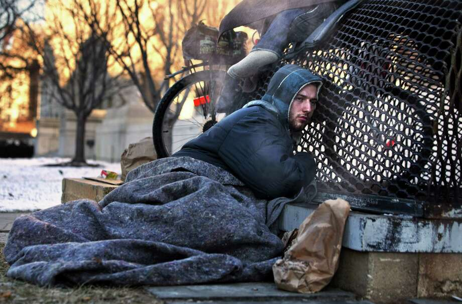 Nicholas Simmons, 20, of Greece, N.Y.,  warms himself on a steam grate with three homeless men by the Federal Trade Commission, just blocks from the Capitol, during frigid temperatures in Washington, Saturday, Jan. 4, 2014.  On New Year's Day, Simmons disappeared from his parents' house in a small upstate New York town, leaving behind his wallet, cellphone and everything else. Four days later, an Associated Press photographer, looking for a way to illustrate unusually cold weather, took his picture as he warmed himself on a steam grate a few blocks from the U.S. Capitol. His parents Paul and Michelle Simmons saw the photograph in USA Today Sunday morning after it was brought to their attention through a Facebook page set up to help find their son, according to police and family friends, and were able to report his location to D.C. police who transported him to a hospital where he was reunited with his father and brother who drove all day to find him. (AP Photo/Jacquelyn Martin)) ORG XMIT: DCJM101 Photo: Jacquelyn Martin / AP