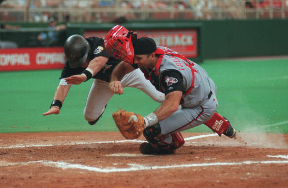 Maximum effort was a hallmark of Craig Biggio's career, as Reds catcher Eddie Taubensee learned during a 1999 game. That playing style fit in well with another Biggio trademark - his pine tar-covered batting helmet, below. Photo: Kerwin Plevka, Staff / Houston Chronicle