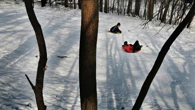 Xavier Cruz, left, 12, and Oscar Turpin III, 14, race each other down a hill at Central Park on Sunday, Jan. 5, 2014 in Schenectady, NY.  (Paul Buckowski / Times Union) Photo: Paul Buckowski / 00025249A