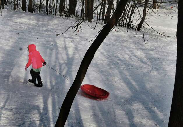 Riley Turpin, 7, drags her sled back up the hill for another slide down at Central Park on Sunday, Jan. 5, 2014 in Schenectady, NY.  (Paul Buckowski / Times Union) Photo: Paul Buckowski / 00025249A