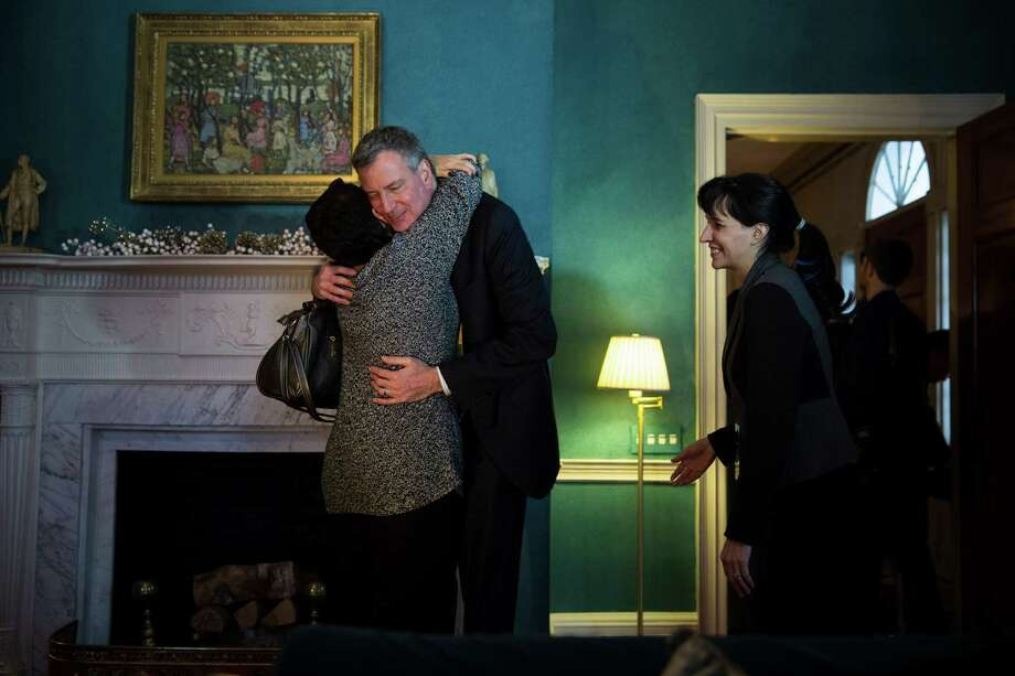 New York Mayor Bill de Blasio hugs a visitor during an open house at Gracie Mansion in New York, Jan. 5, 2014. De Blasio greeted and posed for photographs with thousands of visitors Sunday, concluding a week of inauguration events. (Damon Winter/The New York Times) ORG XMIT: XNYT29 Photo: DAMON WINTER / Damon Winter/The New York Times