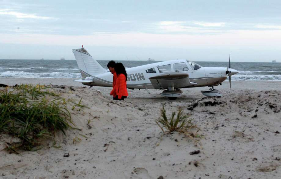 A couple walks past a Piper Cherokee airplane on Stewart Beach in Galveston, Texas, after the pilot made an emergency landing on Saturday evening January 4, 2013. There were four people on board and no injuries were reported. (AP Photo/The Galveston County Daily News, Kevin M. Cox) Photo: Kevin M. Cox, MBR / The Galveston County Daily News