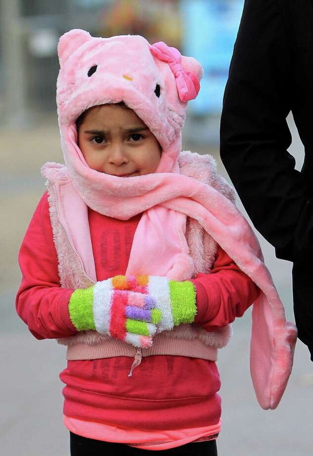 Dana Alaniz, 6, tries to stay warm with a Hello Kitty hat at Discovery Green as temperatures fell Sunday. Photo: Karen Warren, Staff / © 2013 Houston Chronicle