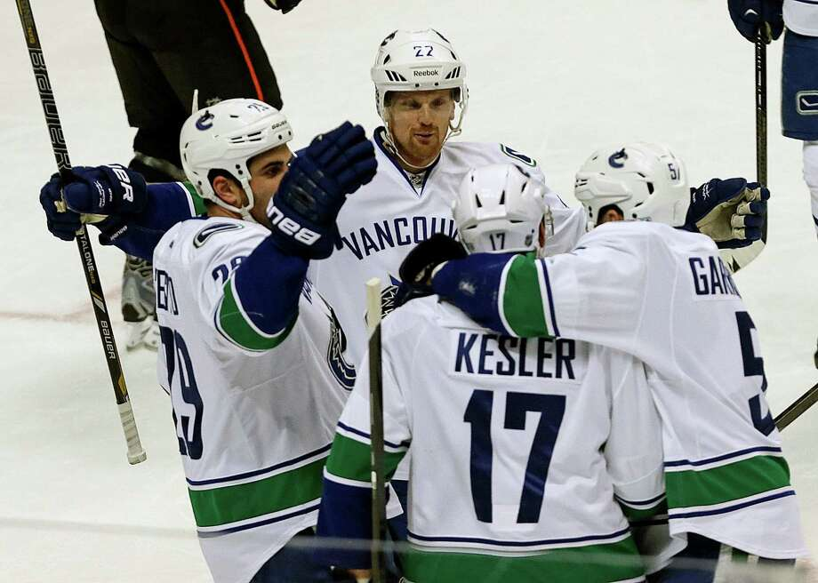 Vancouver Canucks teammates celebrate with center Ryan Kesler (17) on a goal against the Anaheim Ducks in the first period of an NHL hockey game in Anaheim, Calif., Sunday, Jan. 5, 2014. (AP Photo/Reed Saxon) ORG XMIT: ANA102 Photo: Reed Saxon / AP