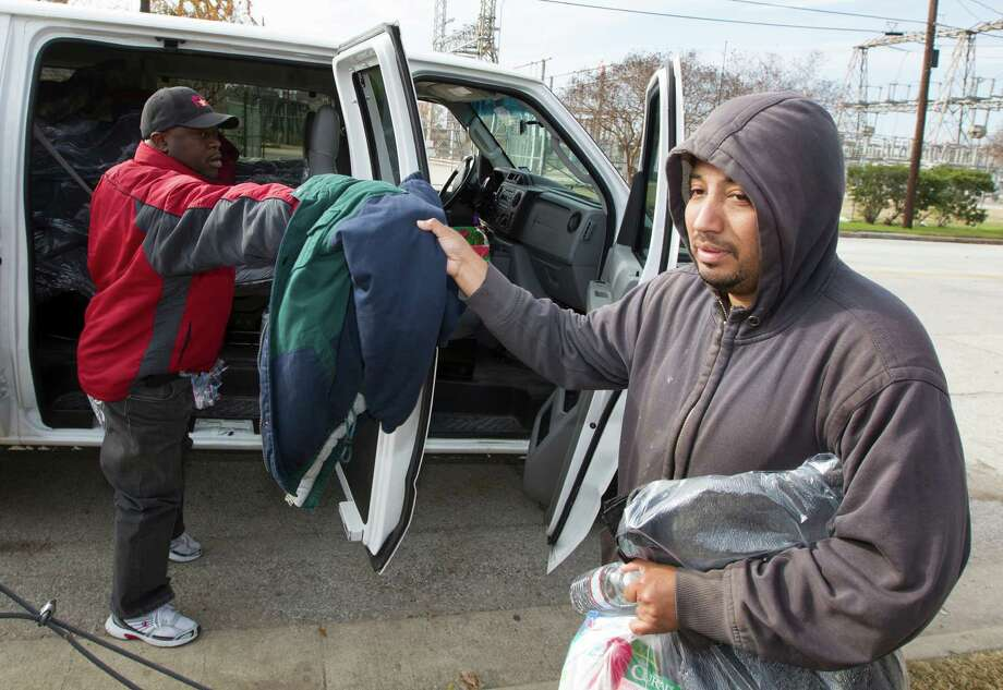 Outreach coordinator for the Star of Hope Charles Williams, left, helps prepare Erick Ponce, who has been homeless for two months and has been staying in his car, prepare for the cold nights ahead. Photo: J. Patric Schneider, Freelance / © 2014 Houston Chronicle