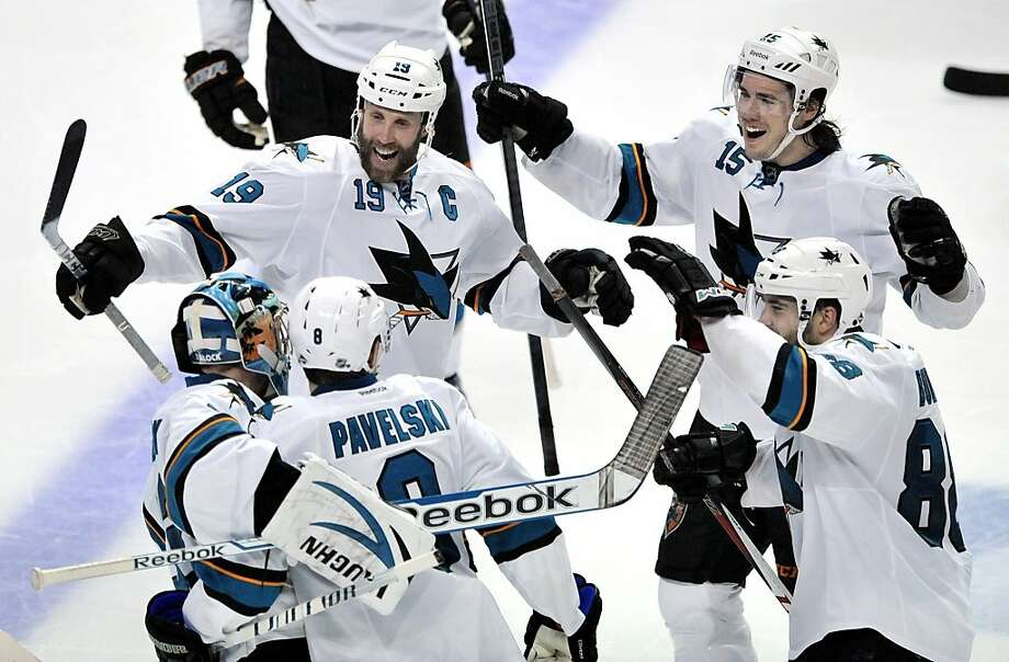 Goalie Alex Stalock celebrates with Joe Thornton (19), James Sheppard (15), Brent Burns (88) and Joe Pavelski after Pavelski's shootout goal clinched the Sharks' victory in Chicago. Photo: Paul Beaty, Associated Press