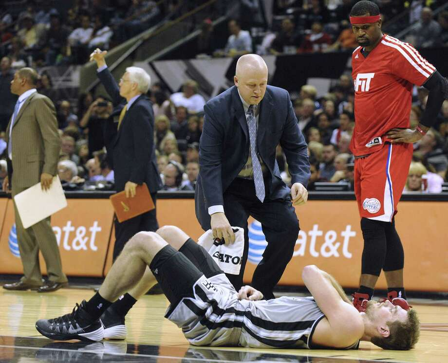 Spurs center Tiago Splitter is attended to by trainer Will Sevening after spraining his right shoulder in Saturday night's win over the Clippers as former teammate Stephen Jackson (right) looks on. Photo: Billy Calzada / San Antonio Express-News / San Antonio Express-News