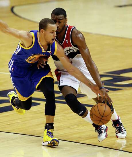 Warriors guard Stephen Curry, left, goes for a steal against the Wizards' John Wall. Photo: Alex Brandon, STF / AP
