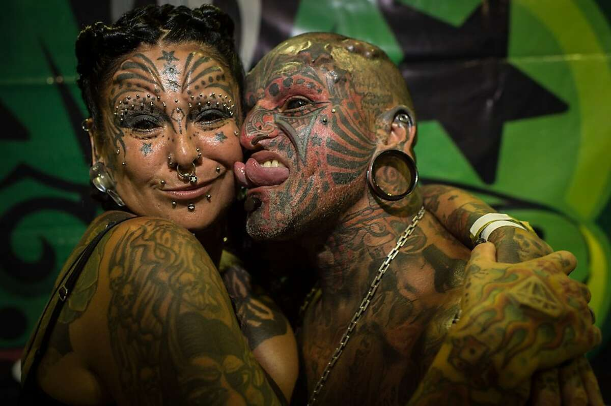 We were made - and remade - for each other: Victor Hugo Peralta hugs his wife, Gabriela Peralta, at Tattoo Week Rio in Rio de Janeiro. The pair are registered by Guinness World Records as the married couple with most body modifications.