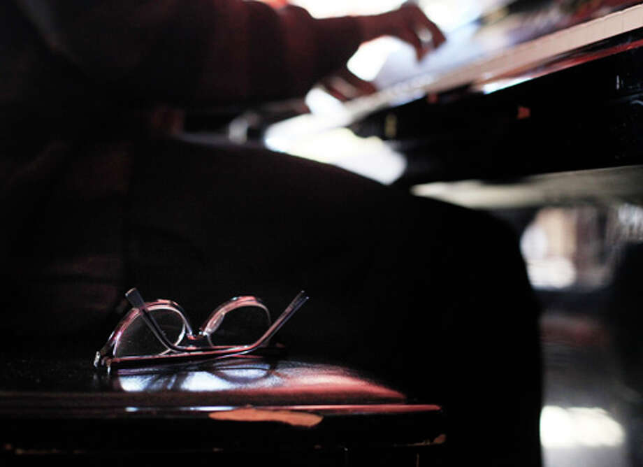 Walter Earl's glasses rest at his side as he plays piano at the Revolution Cafe on Wednesday January 1, 2014 in San Francisco, Calif. Photo: Mike Kepka, The Chronicle / ONLINE_YES