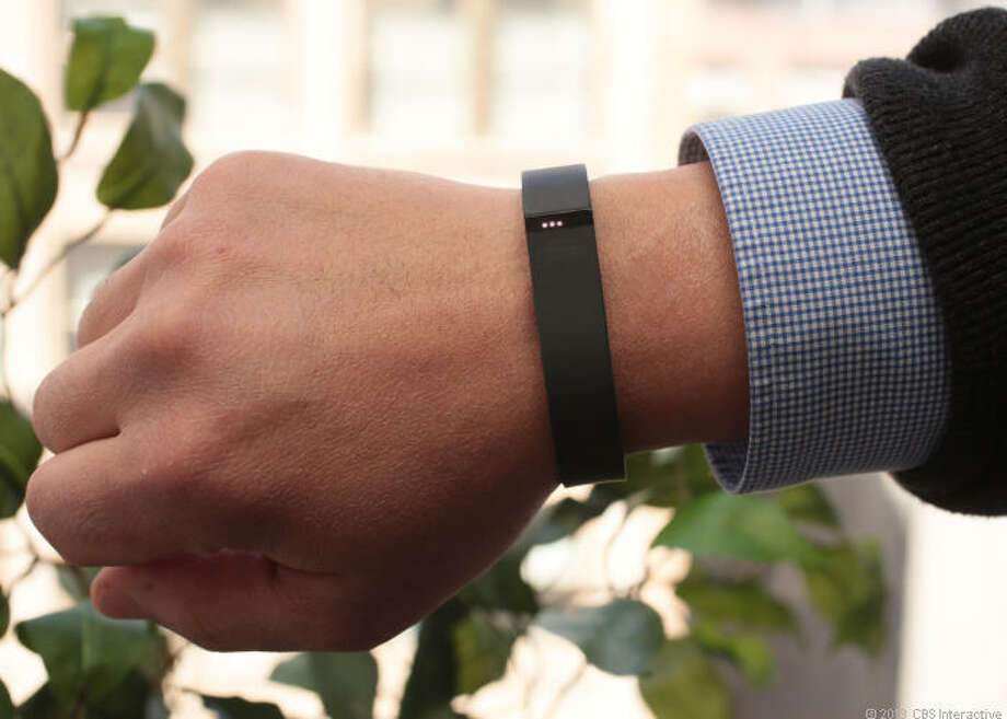 The Fitbit Flex is a wristband that tracks steps, distance, active minutes, and calories burned. Lights on the device track the wearer's progress toward a goal. It tracks sleep quality and wakes its wearer up with a silent, vibrating alarm in the morning. Photo: Cnet / ONLINE_YES