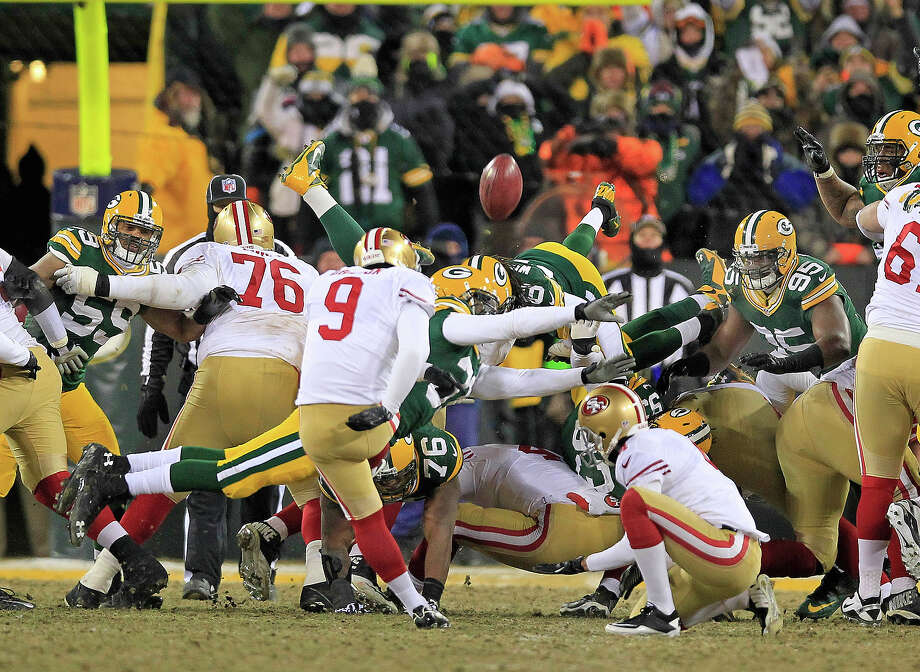 San Francisco 49ers kicker Phil Dawson (9) kicks his game-winning field goal through the arms of Green Bay Packers cornerback Davon House (31) as the 49ers' 23-20 win at the conclusion of an NFL wild-card playoff football game, Sunday, Jan. 5, 2014, in Green Bay, Wis. Photo: Rick Wood, ASSOCIATED PRESS / AP2014