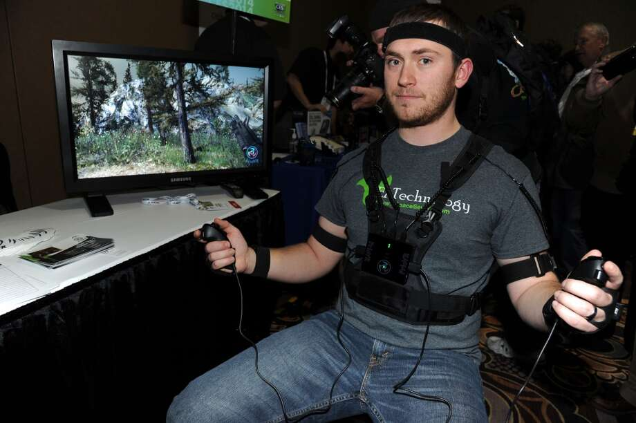 """Chris George wears the PrioVR full body harness with 17 body and head sensors each containing a magnetometer, gyroscope and accelerometer to translate body motion into action by gaming characters, by Yei Technologies at the """"CES: Unveiled,"""" media preview for International CES. Photo: ROBYN BECK, AFP/Getty Images"""