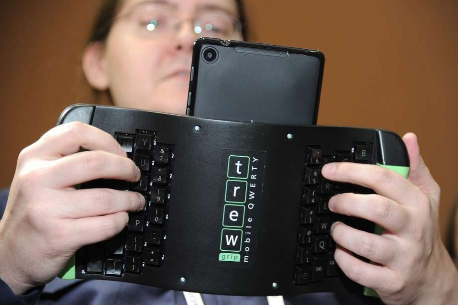 "Robert Price of TREWGrip LLC demonstrates a TREWGrip handheld rear-type keyboard and air mouse for Apple and Android tablets at the ""CES: Unveiled."" Photo: ROBYN BECK, AFP/Getty Images"