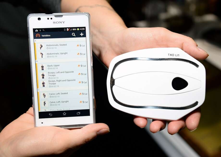 The Tao Wellness WellShell (R) is pictured with a phone displaying information from the device at a CES press event. Photo: Ethan Miller, Getty Images
