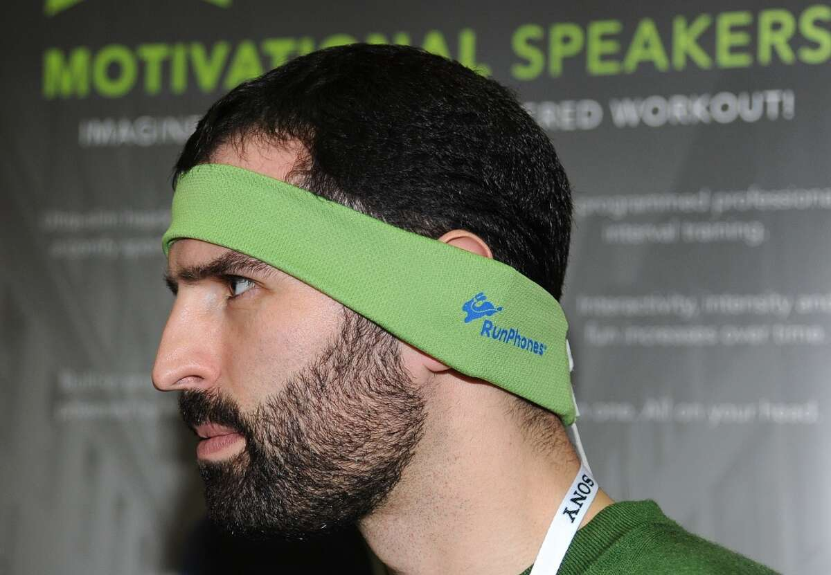 """Casey Macioge representing AcousticSheep LLC wears a RunPhones headband, a moisture wicking headband with removable headphones at the """"CES: Unveiled,"""" media preview for International CES."""
