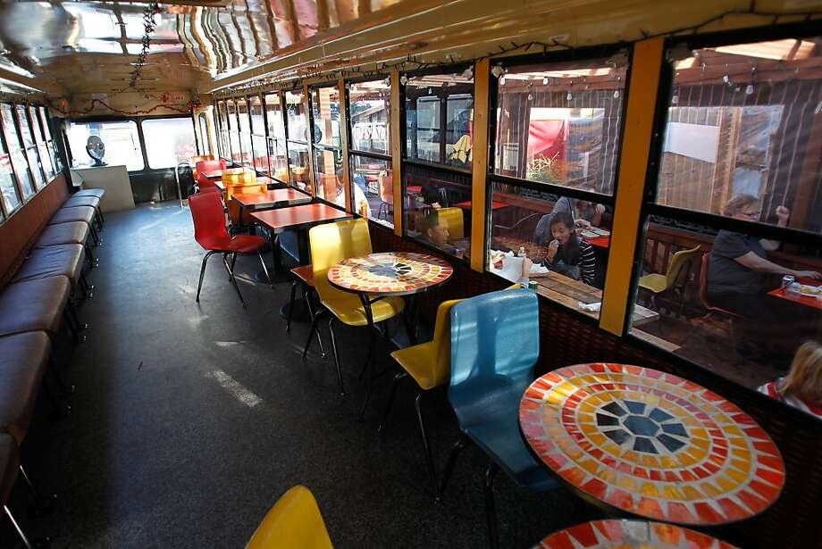 SoMa StrEat Food Park in S.F. offers indoor tables, inside a converted school bus, as well as outside along with food trucks. Photo: Mathew Sumner, Special To The Chronicle