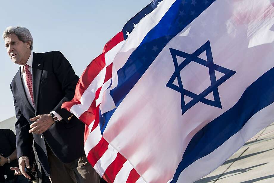 Secretary of State John Kerry walks past U.S. and Israeli flags as he prepares to fly back home from negotiations in Tel Aviv. Photo: Brendan Smialowski, AFP/Getty Images