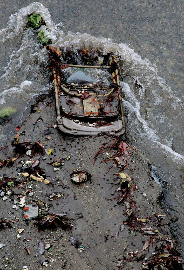 Water flows past a discarded folding chair and other debris in the San Antonio River Monday, Jan. 6, 2014, as the San Antonio River is drained near Nueva Street. The river is drained to remove sediment and perform routine maintenance. Photo: JOHN DAVENPORT, SAN ANTONIO EXPRESS-NEWS / ©San Antonio Express-News/Photo may be sold to the public