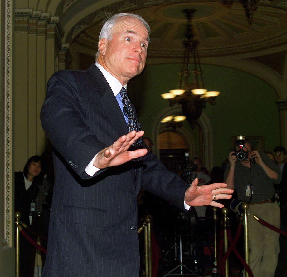 US Senator John McCain (R-AZ) gestures to the waiting media outside the US Senate floor where the impeachment trial of US President Bill Clinton started 14 January on Capitol Hill, Washington. Photo: TIM SLOAN, AFP/Getty Images / AFP