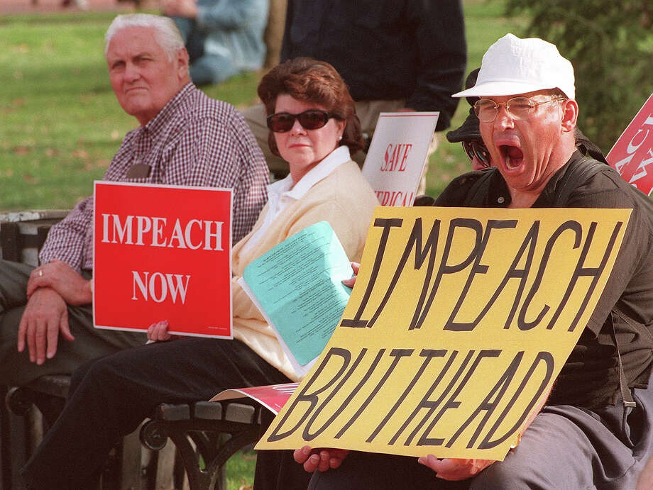 Unidentified protestors demanding the impeachment of US President Bill Clinton conduct their noontime protest from the park benches in Lafayette Park across from the White House. Photo: PAUL J. RICHARDS, AFP/Getty Images / AFP