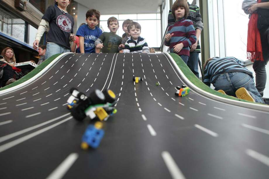 Children, from left, Ale Raptopoulos, 8, of Trumbull, Jameson Castro, 6, of Bridgeport, Evan Scheffler, 6, of Bridgeport, and Maxwell Durden, 5, of Trumbull, race lego cars at the Discovery Museum Lego Block Party on Sunday, January 13, 2013.  The proceeds support the museum's outreach programs to Bridgeport school programs. Photo: B.K. Angeletti / Connecticut Post