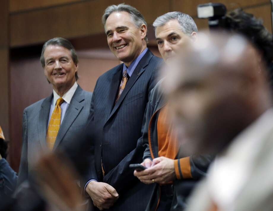 Texas president Bill Powers, left, and athletic director Steve Patterson, center, listen as Charlie Strong, right, answers questions. Photo: Eric Gay, Associated Press