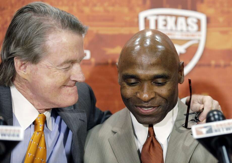 Charlie Strong, right, is hugged by Texas president Bill Powers, left, during the news conference. Photo: Eric Gay, Associated Press