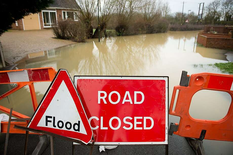 Soggy ol' England:Warning signs state the obvious in Tewkesbury, Gloucestershire, which was expecting more rain after several storms. Photo: Leon Neal, AFP/Getty Images
