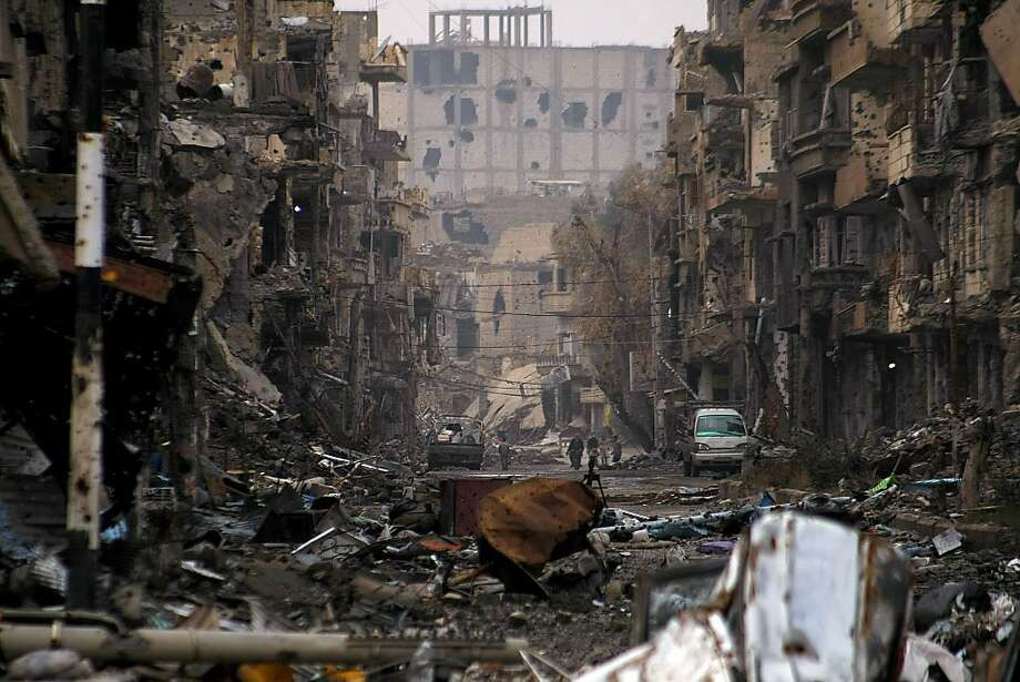 "The rebels' other enemy:Syrians walk among shelled buildings in the northeastern city of Deir Ezzor. Syrian rebels vowed to capture and kill dozens of jihadists in a new ""revolution"" against an al-Qaida affiliate they accuse of worse abuses than their hated president, Bashar al-Assad. Photo: Ahmad About, AFP/Getty Images"