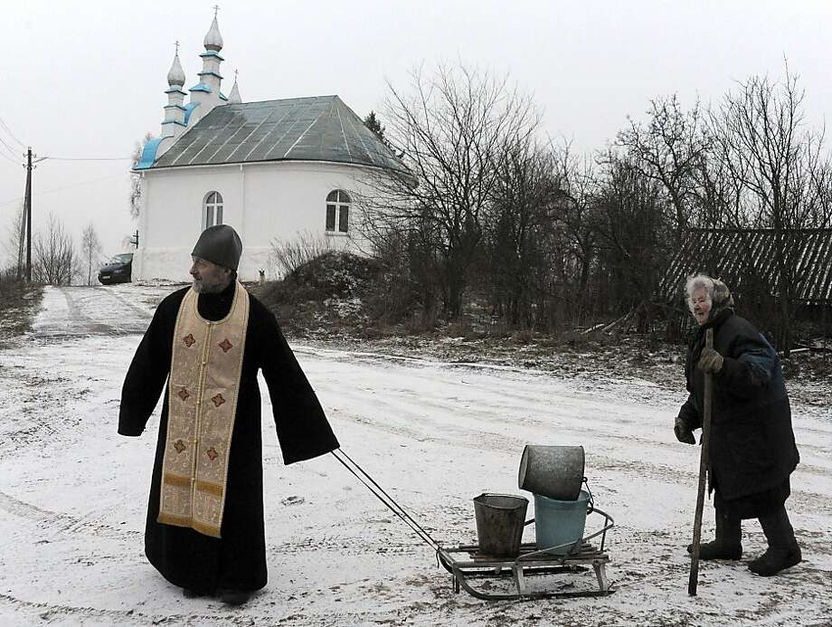 The father lends a hand: A Belarusian Orthodox priest pulls a sled laden with an elderly woman's water buckets in the village of Kasun, 