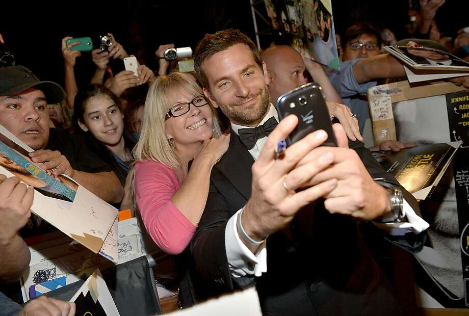 Me and Brad: Actor Bradley Cooper makes a fan happy by snapping a selfie on her phone at the Palm Springs International Film Festival in 