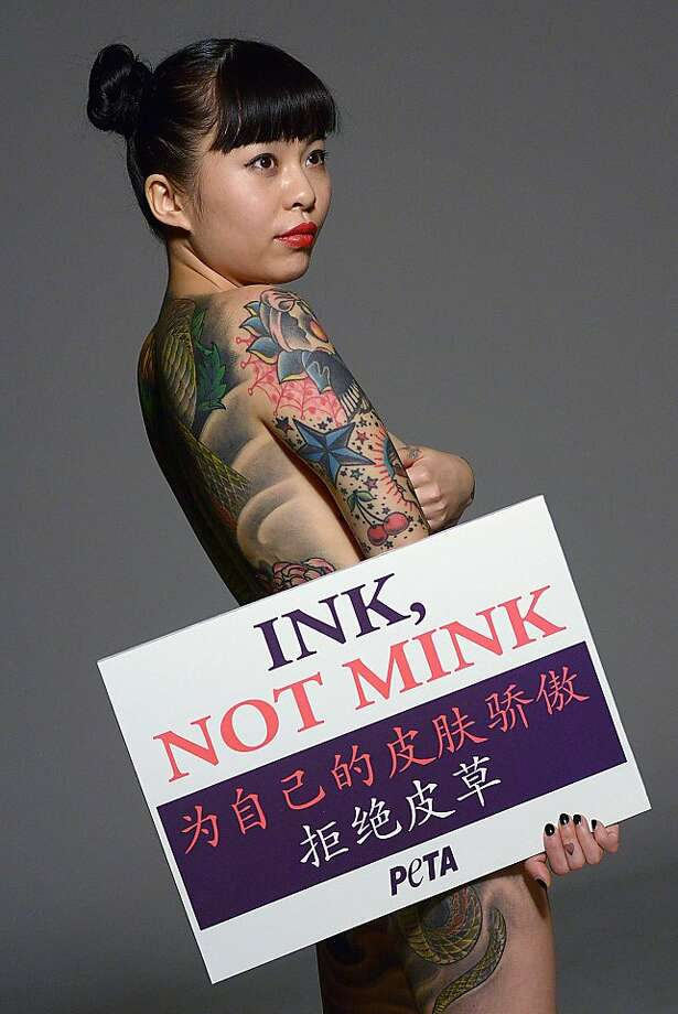 Anti-mink, pro-ink:In Beijing, Chinese tattoo artist Wang Ke promotes tattoos as an alternative to wearing fur during an advertising shoot for PETA. Photo: Wang Zhao, AFP/Getty Images