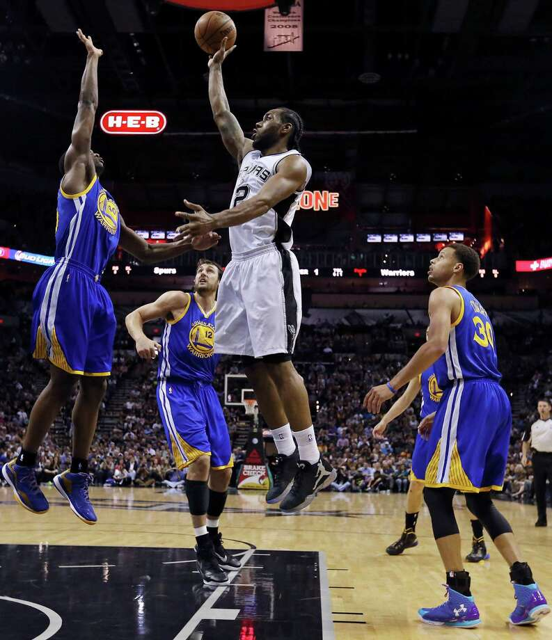 San Antonio Spurs' Kawhi Leonard shoots between Golden State Warriors' Harrison Barnes (from left), Andrew Bogut, and Stephen Curry during first half action Sunday April 5, 2015 at the AT&T Center. Photo: Edward A. Ornelas, San Antonio Express-News / © 2015 San Antonio Express-News