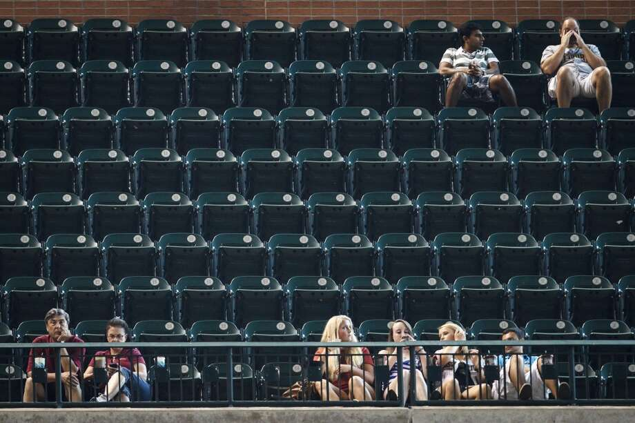 Fans watch the baseball action in a nearly empty section during the fifth inning of a Houston Astros. At one time it was so hot in Houston that some people went to baseball games just to stay cool. Photo: Michael Paulsen, Houston Chronicle