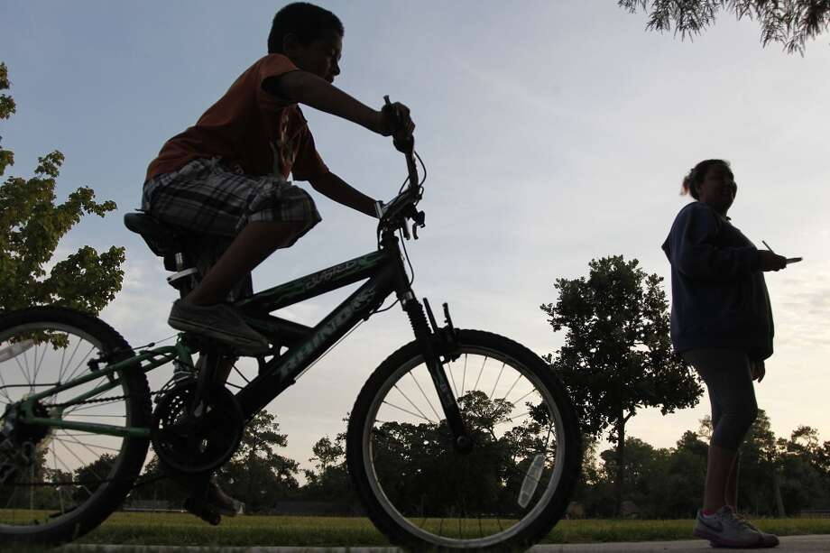 Andres Arredondo, 7, rides with his mother Ana Arredondo, 33, early in the morning at Nob Hill Park on Monday, Aug. 13, 2012, in Houston, TX. Partly sunny and high temperatures are expected through out the week.  ( Mayra Beltran / Houston Chronicle ) Photo: Mayra Beltran, Houston Chronicle