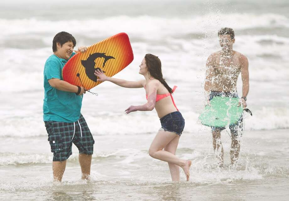 Cameron Heth, center, pushes Justin Perez, left, both of Cypress, after he splashed her as they visit Stewart Beach, Wednesday, April 17, 2013, in Galveston. ( Nick de la Torre / Chronicle ) Photo: Nick De La Torre, Chronicle