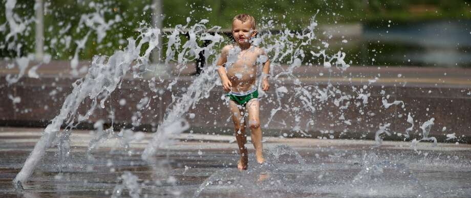 Ian Niggli, 3, runs through the fountains at Discovery Green, Wednesday, May 8, 2013, in Houston.  He was out with his little sister and grandparents enjoying the warm temperatures downtown Houston.  ( Karen Warren / Houston Chronicle ) Photo: Karen Warren, Houston Chronicle
