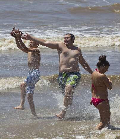 Jacob Barboza, left, and James Martin, both of Spring, play football with friends on the beach along Seawall Boulevard, Saturday, June 29, 2013, in Galveston. ( Nick de la Torre / Houston Chronicle ) Photo: Nick De La Torre, Houston Chronicle