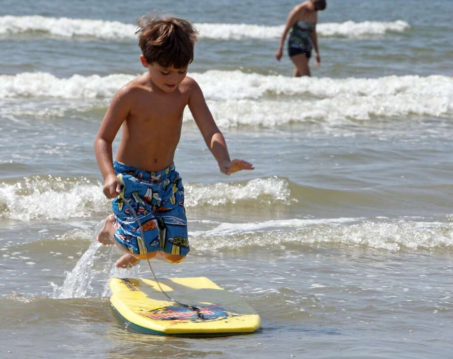 Six-year-old Carter Burnett jumps onto a body board near Beach Town Saturday, Aug. 31, 2013, in Galveston.( James Nielsen / Houston Chronicle ) Photo: James Nielsen, Houston Chronicle