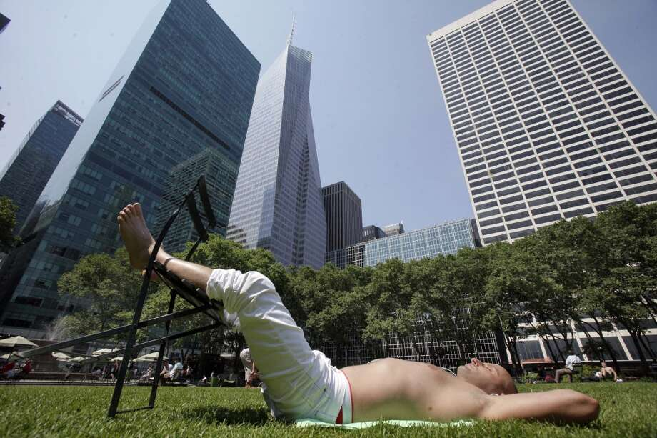 Cemal Yetkiner, from Turkey, takes in the sun in New York's Bryant Park, Wednesday, June 8, 2011. The official start of summer is still two weeks away, but much of the nation is sweating through near-record temperatures, with heat advisories and warnings issued across the Northeast, mid-Atlantic and upper Midwest on Wednesday. (AP Photo/Richard Drew) Photo: Richard Drew, Associated Press