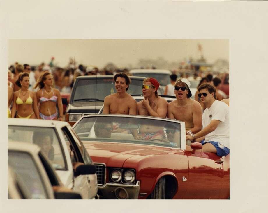 Gary Carmouche, Shawn Demery, Troy Cody, and Al Reiloy cruise for the sites on West Beach of Galveston Island Sunday. March 24, 1991. Photo: Gaylon Wampler, Houston Chronicle
