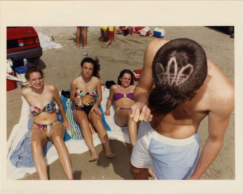 "Chris Caldwell shows off his new ""do"" as he and some friends from Kingwood High School got a jump on spring break at Galveston's West Beach today. The emblem is the Adidas logo. March 6, 1991. Photo: Micheal Boddy, Houston Chronicle"