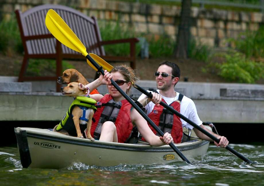 Kacie Broadhurst and Joe Pattavina, of The Woodlands,  enjoy sunny skies and warm weather as they paddle on The Woodlands Waterway with their dogs, Carmella and Annie, on Sunday, April  24, 2011  in The Woodlands, Texas. (AP Photo/The Courier, Karl Anderson) Photo: Karl Anderson, AP