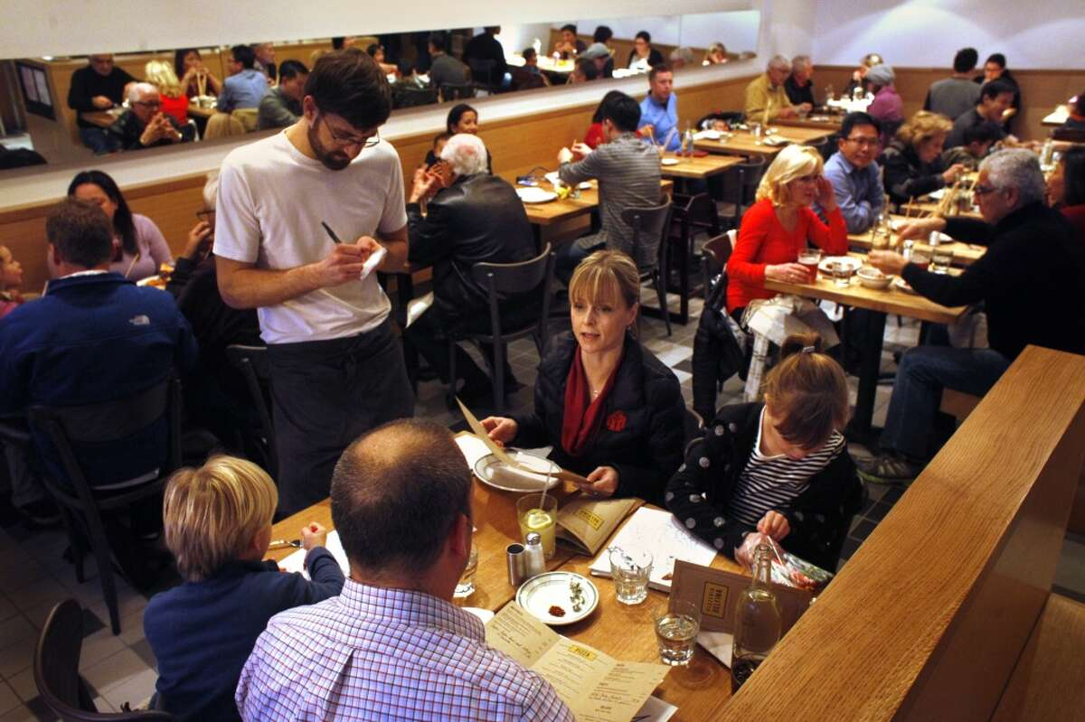 Waiter Eric Richter takes customers orders at the new Pizzeria Delfina, Tuesday December 31, 2013, in Burlingame, Calif.