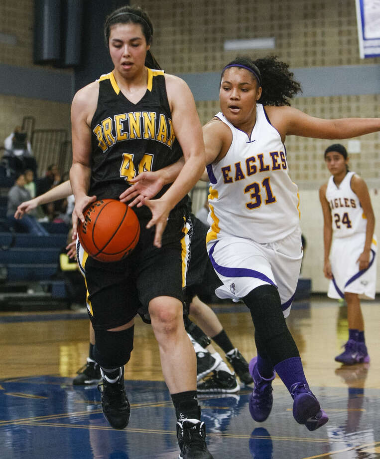 Brackenridge's Skyler Reyna, right, tries to take the ball from Brennan's Eliza Martinez at the Lanier Alumni Center  Saturday. Brennan won the game, 79-37. Photo: Marvin Pfeiffer / Southside Reporter / Prime Time Newspapers 2013