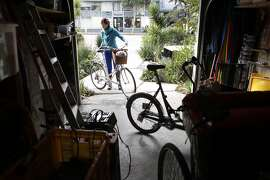 Kimberly Conley puts a bicycle into her garage where she and her husband keep their bicycles and other items rather than cars, Monday January 6, 2014, in San Francisco, Calif. They have turned their driveway into a parklet for public uses.